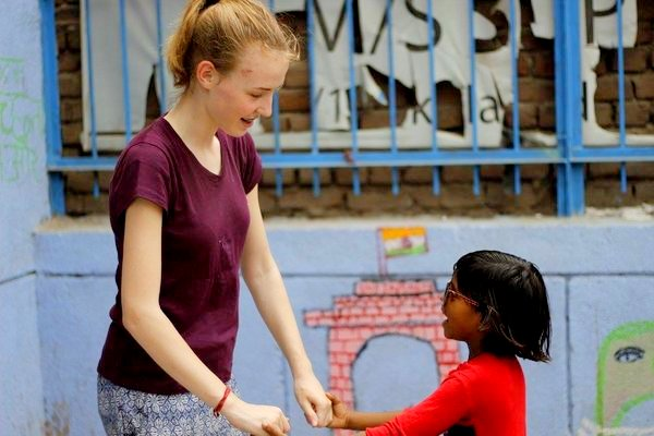 julia with kid while volunteering in India